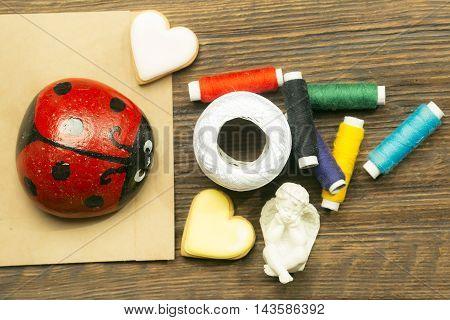 Bobbins of thread with red ladybug decorative hearts and angel figure