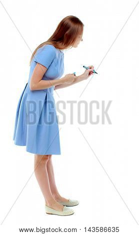 back view of writing beautiful woman. Rear view people collection.  backside view of person. Isolated over white background. Skinny girl in a blue dress writes marker. side view