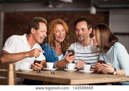 Friendly air. Positive and smiling men and women using their smart phones while sitting at the table and drinking good coffee