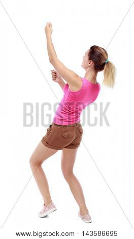 back view of standing girl pulling a rope from the top or cling to something. girl  watching. Rear view people collection.  backside view of person.  Isolated over white background. Sport blond in