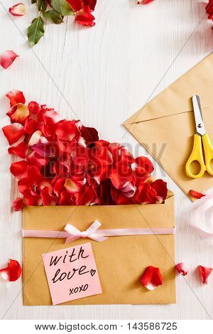 Handmade love message with flowers, copy space. Paper, scissors, envelope and red rose petals composition with love note, white background, free space