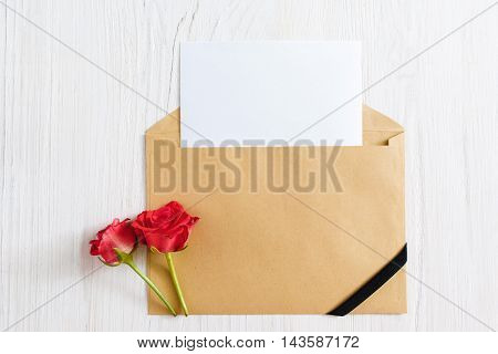 Opened envelope with blank paper and black ribbon with two roses, flat lay. Mourning, funeral, sorrow concept