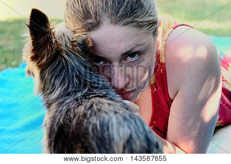 Freckled girl with a yorkshire terrier in the garden