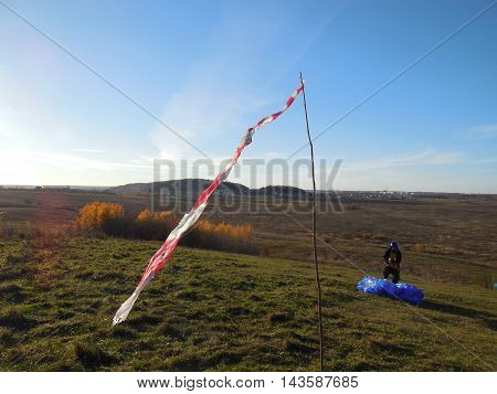 wind cone and paraglider on a slope. West wind on the mountain Mozhayskaya, Leningrad region, Russia