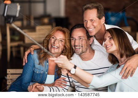Be positive. Close up of merry and delighted friends making selfie photos using mono stick