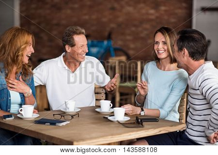 Be happy. Happy and smiling men and women having fun while being indoors, drinking coffee and sitting at the table