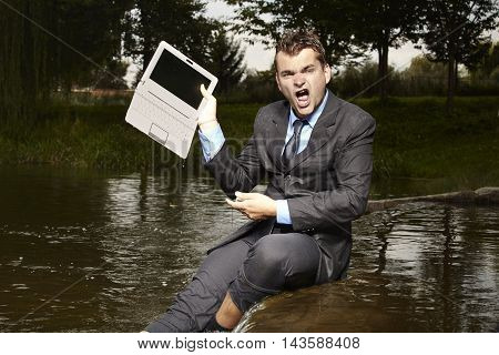 Crazy businessman in suit is mad of broken notebook