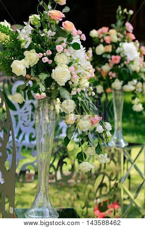 Wedding flower bouquet of beautiful natural tender pink white and creamy roses with green leaves in long glass vase floral decoration outdoor