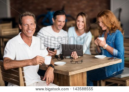 During the day. Cheerful and content man holding cup of coffee with his friends using phone and tablet in background