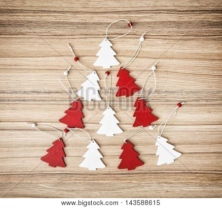 Red and white decorative christmas trees on the wooden background. Yuletide theme. Symbolic objects.