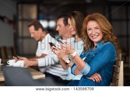 Digital generation. Positive and merry woman holding smart phone and laughing with another people using phones in background