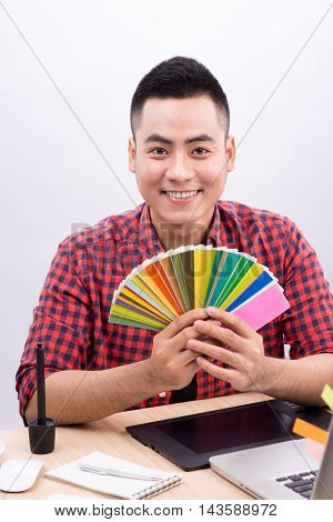 Happy asian male graphic designer holding color fan in his hand