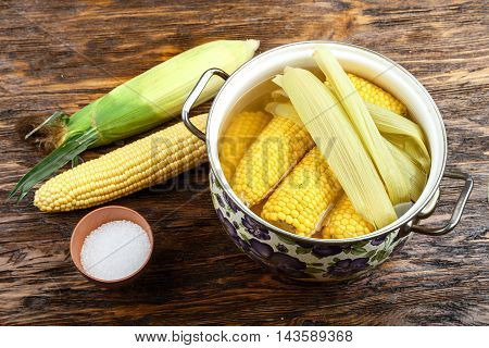 Cooked and raw corncobs on a dark wooden background.