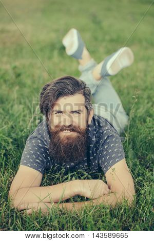 Bearded Man Laying On Green Grass Smiling
