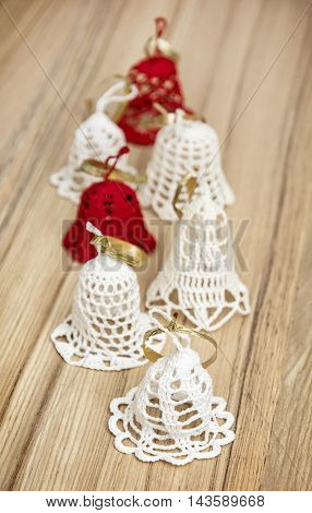 Beautiful red and white crochet christmas bells on the wooden background. Merry Christmas. Vertical composition.