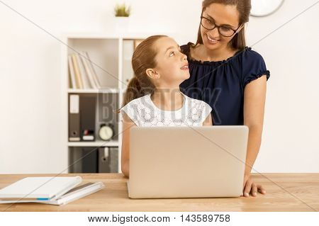 Mother helping her little daughter how to use a computer