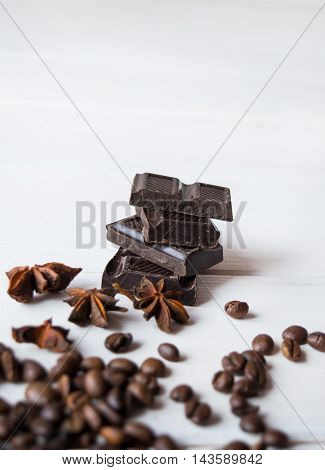 Coffee beans and anis and chocolate on the wooden table.
