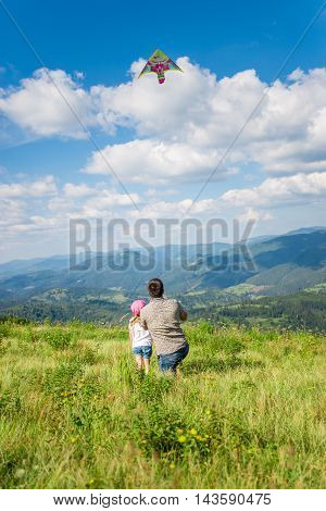 Dad and daughter launch a kite against the backdrop of beautiful views of mountains and sky. Vertical