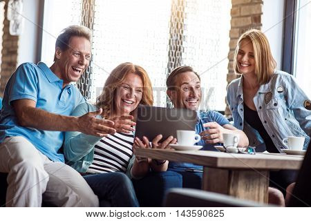 Laughable. Smiling and positive group of people using digital tablet together while drinking coffee in cafe