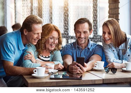 Keeping in touch. Happy and merry group of people using smartphone while drinking together coffee in cafe and having good time