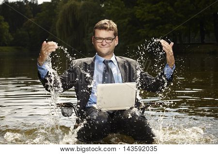 Businessman in suit relaxing after burning out in summer water