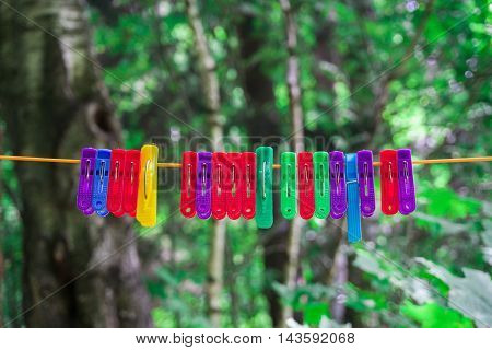 colored clothes pegs hanging on a rope in the street