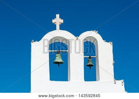 White bell tower over a blue sky in Santorini - Greece