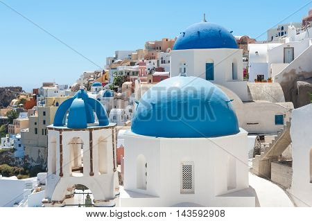 View of Oia in Santorini with a blue dome - Greece