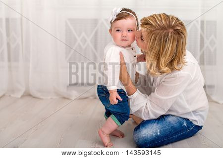 Young mother spending time at home with her little daughter. Mom and daughter dressed in white shirt and jeans