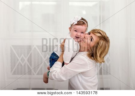 Mom kisses her little daughter on the cheek. Mom and daughter dressed in white shirts and jeans