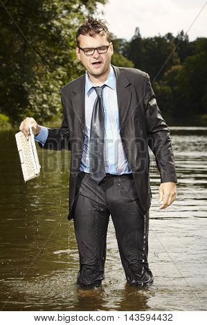 Crazy businessman in suit and tie saving notebook from water