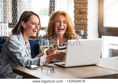 Girls party. Cheerful and merry women using laptop and drinking champagne