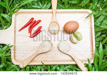 Rice in wooden spoon with food ingredients on the tray with green grass background