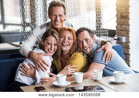 Best friends. Delighted and happy group of friends embracing each while being in cafe
