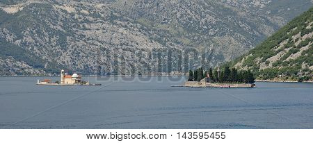 The islands of Our Lady of the Rock on the left and St George's Abbey on the right in Kotor Bay Montenegro. The former was artificially created by locals using rocks the later is also known as the Island of the Dead and contains a 12th century Benedictine
