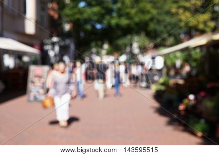 defocused group of people walking through pedestrian shopping street. blurred background.