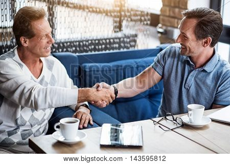 Friendly coworkers. Two cheerful and confident colleagues drinking coffee and clasping hands