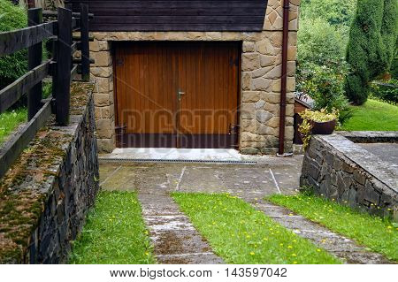 Driveway to wooden garage doors with grass