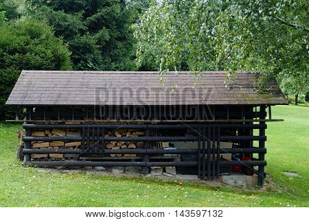Old garden shed with firewood and ladder