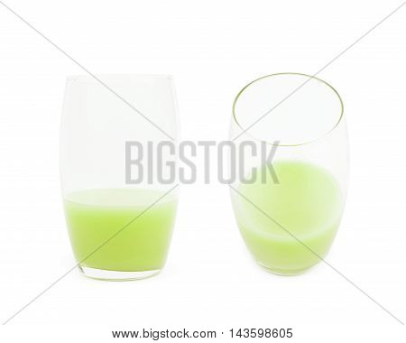 Tall glass half-filled with the green colored juice isolated over the white background set of two different foreshortenings