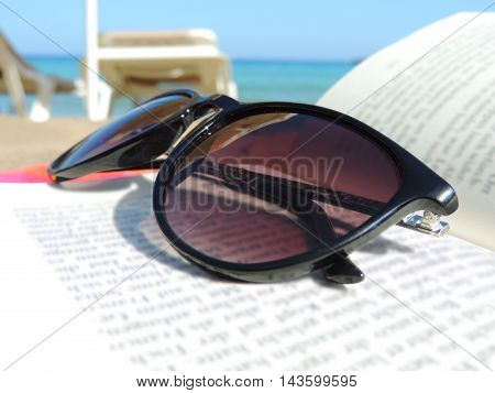 Reading at the beach. Sunglasses and book with selective focus.