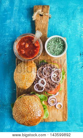 Homemade beef burgers with onion rings, fresh vegetables, spices and tomato sauce on rustic serving wooden board over blue painted background. Top view, vertical composition