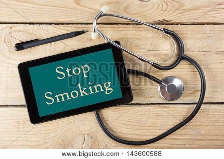 Stop Smoking - Workplace of a doctor. Tablet, medical stethoscope, black pen on wooden desk background. Top view.