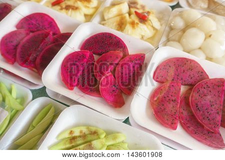 sliced tropical fruits wrapped with plastic sheet on market display.
