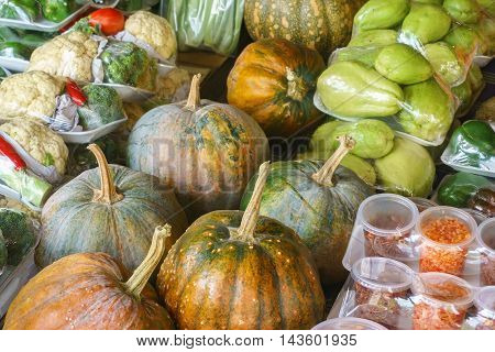 Assorted vegetables at market display wrapped with plastic sheet.