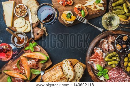 Italian wine antipasti snack variety over dark background, top view, copy space, horizontal composition