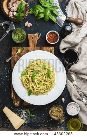 Italian pasta dinner. Spaghetti with pesto sauce and fresh basil, Parmesan cheese and spices served with glass of wine on rustic wooden board over dark grunge plywood background, top view