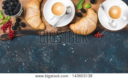 Breakfast set. Freshly baked croissants with garden berries and coffee cups on rustic wooden board over dark grunge plywood backdrop, top view, copy space