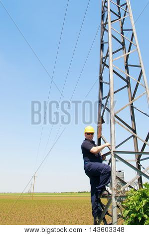 Electrician in yellow helmet working on electric power pole