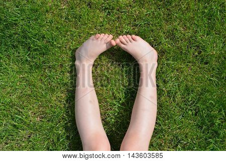 Children's feet on the green grass. Summertime.